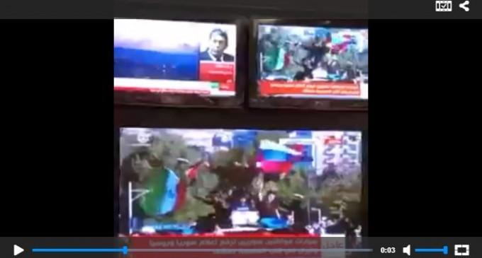 Les syriens chantent et agitent les drapeaux de la Syrie Russie et de l'Iran