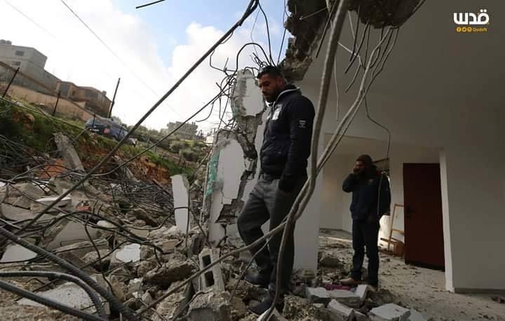 Les membres de la famille Abul-Haija se trouvent sur les décombres de leur maison qui ont été détruits par les forces d'occupation&