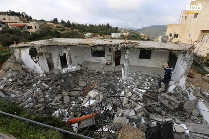 Les membres de la famille Abul-Haija se trouvent sur les décombres de leur maison qui ont été détruits par les forces d'occupation