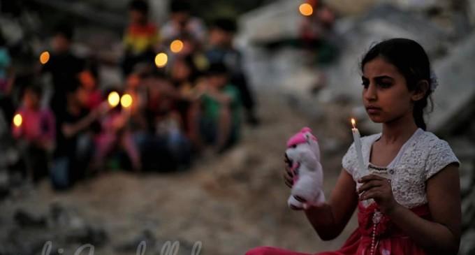Les enfants palestiniens allument des bougies sur des décombres de maisons, démolis dans la dernière agression israélienne sur Gaza, en mémoire aux 27 vies assassinées par les machines d'Israël.