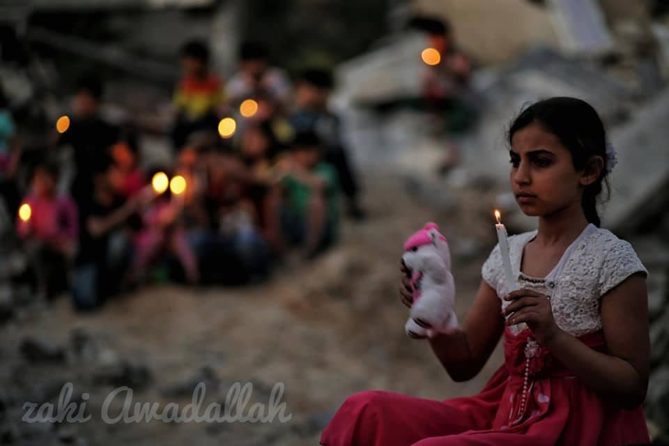 Les enfants palestiniens allument des bougies sur des décombres de maisons, démolis dans la dernière agression israélienne sur Gaza, en mémoire aux 27 vies assassinées par les machines d'Israël