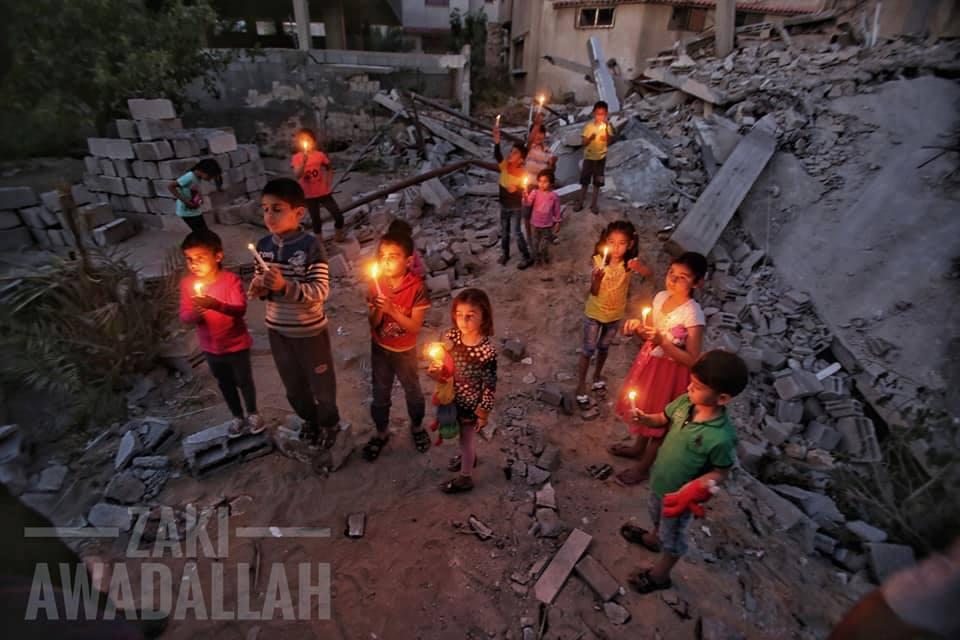 Les enfants palestiniens allument des bougies sur des décombres de maisons, démolis dans la dernière agression israélienne sur Gaza, en mémoire aux 27 vies assassinées par les machines