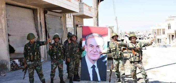 Images | Les soldats de l'Armée Arabe Syrienne élèvent le drapeau Syrien et le portrait du défunt Président Hafez Al Assad à Khan sheikhoun