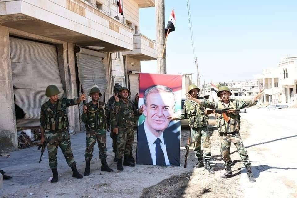 Les soldats de l'Armée Arabe Syrienne élèvent le drapeau Syrien et le portrait du défunt Président Hafez Al Assad à Khan sheikhoun.