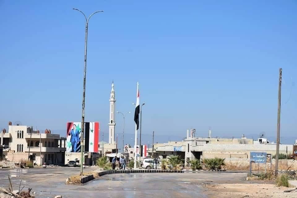 Les soldats de l'Armée Arabe Syrienne élèvent le drapeau Syrien et le portrait du défunt Président Hafez Al Assad à Khan sheikhoun.1