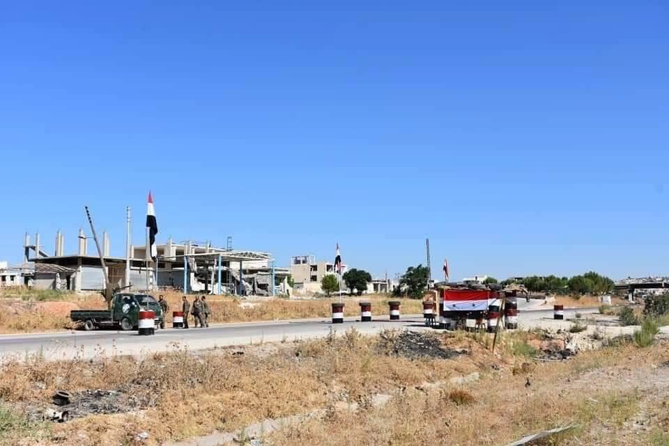 Les soldats de l'Armée Arabe Syrienne élèvent le drapeau Syrien et le portrait du défunt Président Hafez Al Assad à Khan sheikhoun