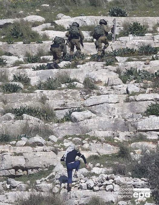 un jeune palestinien suit des soldats israéliens avec une pierre à la main dans la ville de Qafr qaddum dans le nord de la Cisjordanie occupée